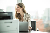 Woman sat at desk with laptop and printer on desk