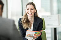Woman sat in office smiling with colour printer in background