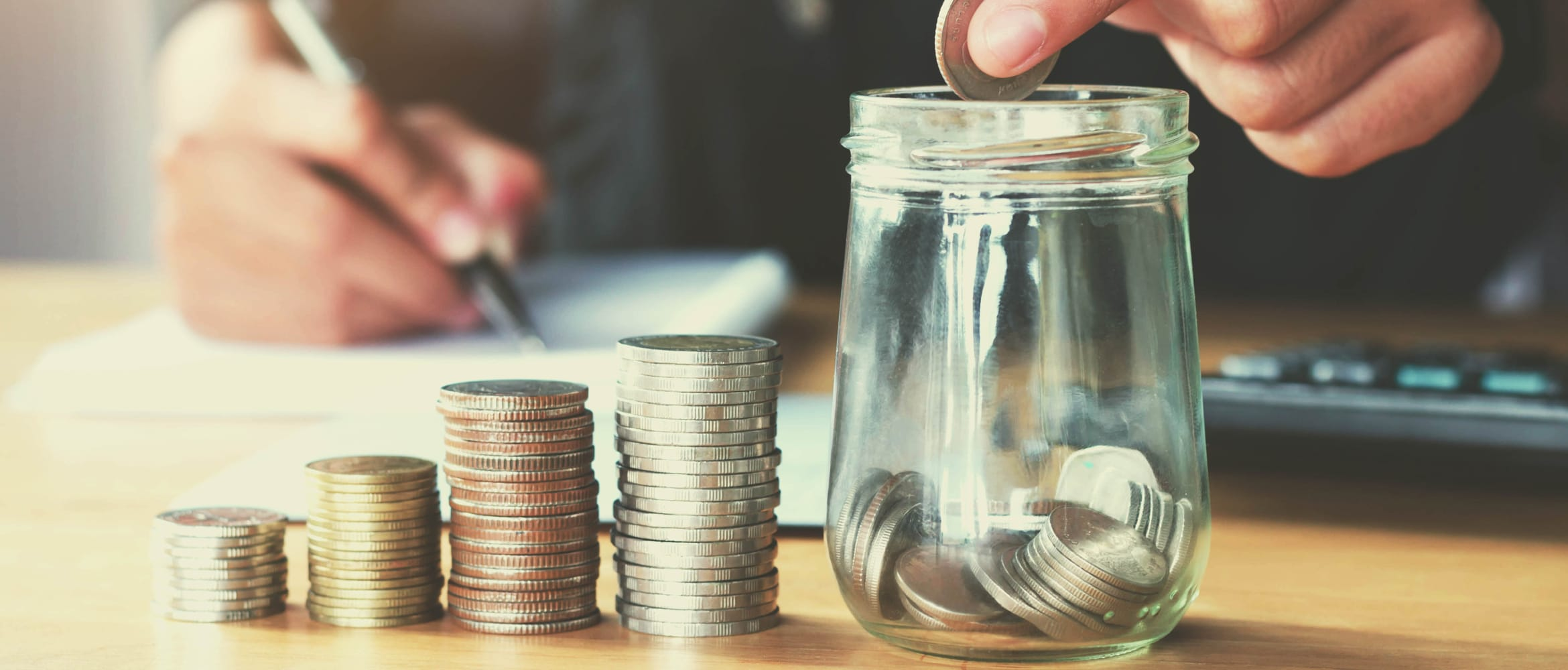 hand placing coins into a jar, to highlight the concept of cost control