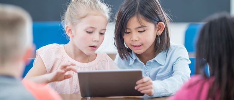 young children using a tablet in a classroom setting