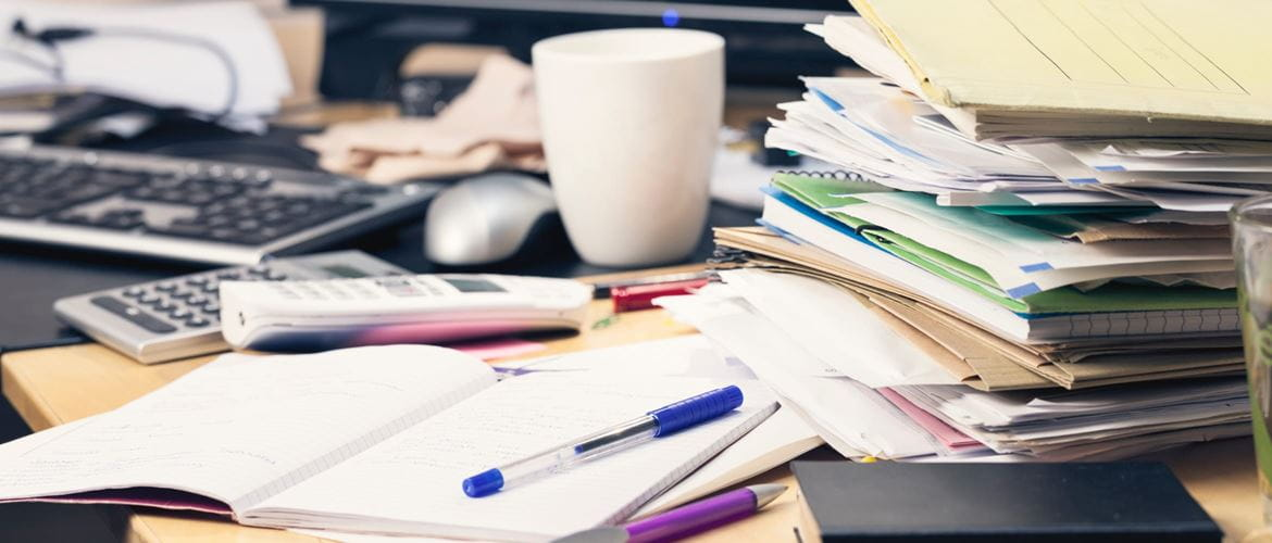 messy office work desk covered in files, cups, papers and pens