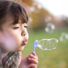 young girl blowing bubbles in a field brother